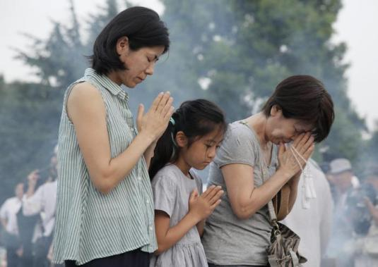 People offer prayers for victims of the 1945 Hiroshima atomic bombing, in front of a cenotaph at the Hiroshima Peace Memorial Peace Park, in Hiroshima, Japan, early morning 06 August 2015. Hiroshima is marking the 70th anniversary of the atomic bombing of the city on 06 August.  ANSA/KIMIMASA MAYAMA